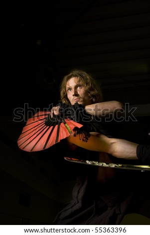 a samurai ready for action with katana and combat fan - stock photo