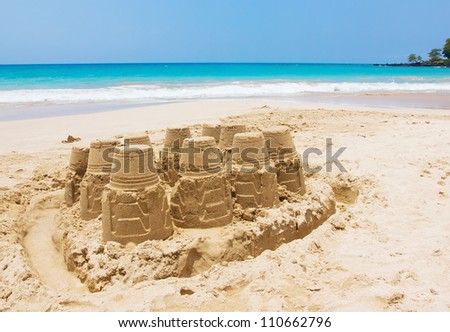 A sand castle at the beach against blue sky and crystal blue water - stock photo