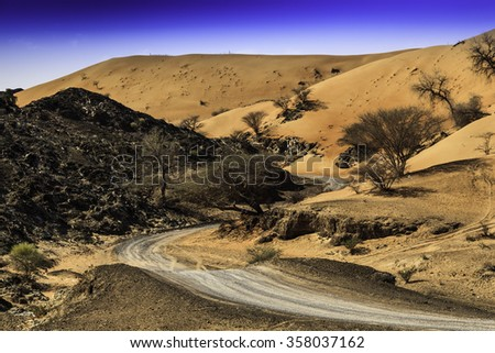 A sand dune close to Wadi Maidaq, Fujairah, UAE in an off road track. This is where sand and rocks meet in UAE. - stock photo