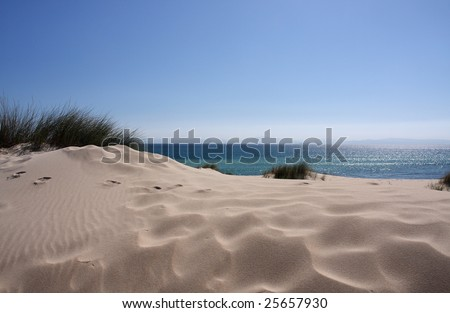 A sand dune in Tarifa, in southern Europe, and the north moroccan mountains in the distance in Africa - stock photo