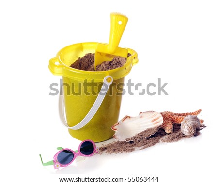 A sand pail filled with sand with a small assortment of seashells and a pair of children's sunglasses.  Isolated on white. - stock photo