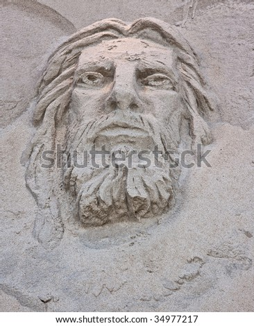 A sand sculpture at the beach of the face of Jesus