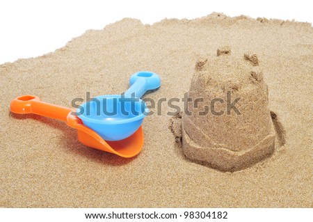 a sandcastle on the sand and each shovels - stock photo