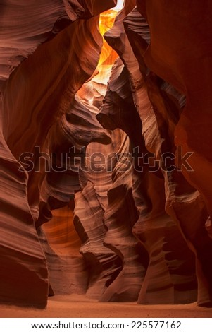 A sandstone rock formed cave with sandy floor showing sun shining through at the top. - stock photo