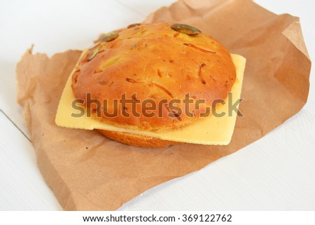 A sandwich with a slice of cheese on the paper and white wooden background - stock photo