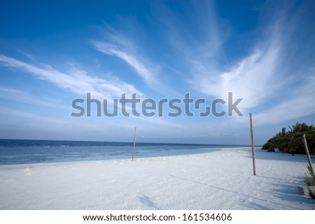A sandy beach with a volleyball net on it. - stock photo
