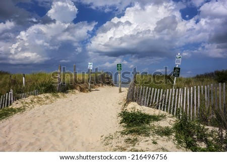 A sandy pathway to beach with dramatic clouds. - stock photo