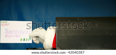 a Santa Claus hand reaches out and holds a  letter from inside a mail box - stock photo
