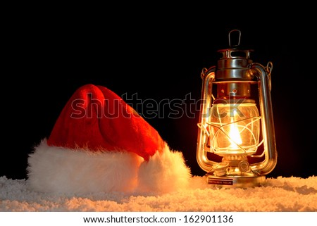 A Santa Claus or Father Christmas hat on snow illuminated by the glow of an oil filled lantern, black background. - stock photo