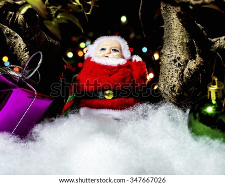 A Santa Claus toy holding on bokeh background