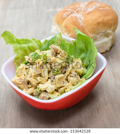 A savory curried chicken salad on lettuce with bun in background.