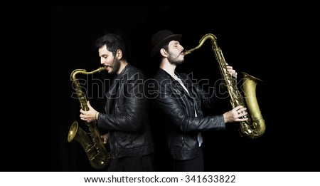 A saxophone players   dark background.  Saxophonist jazz man with Sax. Leather Jacket dressed saxophone players. Music concept.  - stock photo