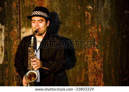 A saxophonist plays outdoors at sunset against a grungy industrail backdrop. - stock photo
