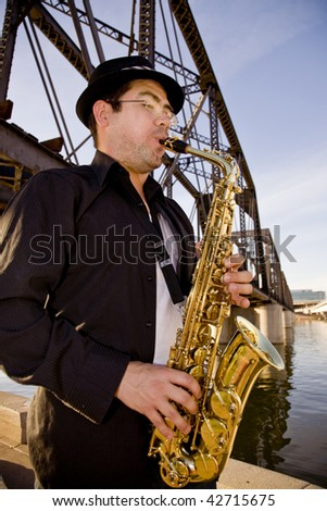 A saxophonist plays outdoors at sunset  against a grungy industrial skyline. - stock photo