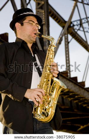 A saxophonist plays outdoors under  and iron trestle railroad bridge. - stock photo