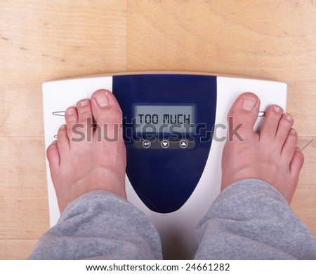 """A scale with two feet of the person standing on it on a wooden floor. The scale says: """"TOO MUCH"""". - stock photo"""