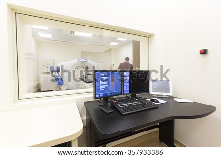 A scanning room with computers and monitors next to the CT scan room in a new modern cancer treatment hospital.