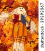 A scarecrow sitting on fall leaf background, scarecrow - stock photo