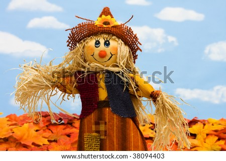 A scarecrow sitting on fall leaves on a sky background, scarecrow - stock photo