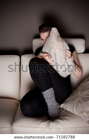 A scared beautiful young woman watching a horror movie at home alone. - stock photo