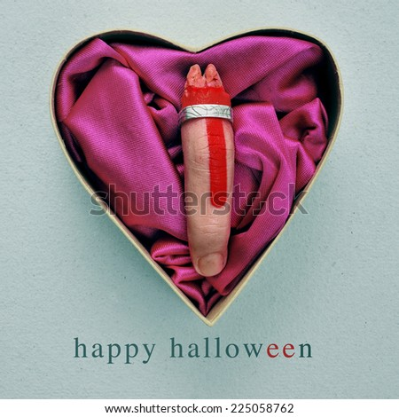 a scary amputated finger with a ring in a heart-shaped gift box, and the text happy halloween - stock photo