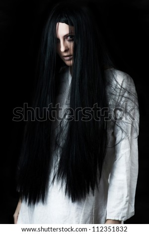 a scary ghost girl wearing a white nightie - stock photo
