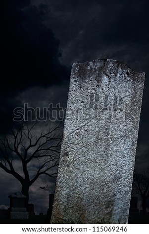 A scary graveyard with a blank grave stone, ready for Halloween. - stock photo