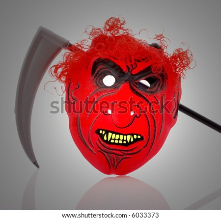 A scary mask and a scythe blade under a spotlight - stock photo