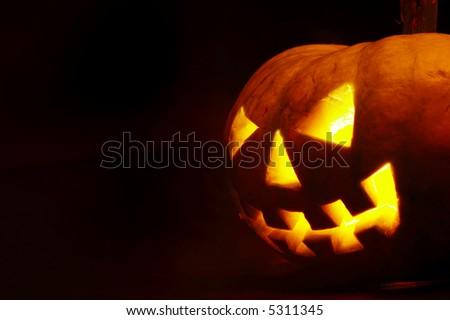 A scary old jack-o-lantern on black. - stock photo