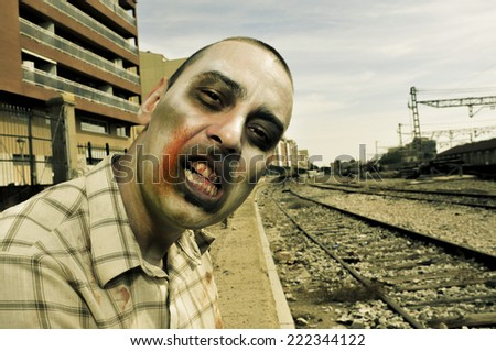 a scary zombie at abandoned railroad tracks, with a filter effect - stock photo