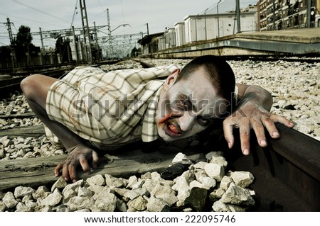 a scary zombie crawling by the railroad tracks - stock photo
