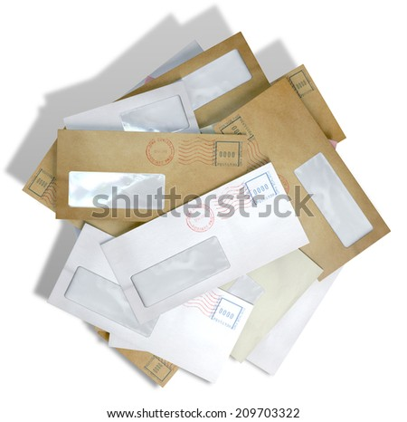 A scattered stack of regular envelopes with delivery stamps and a clear window on an isolated white background - stock photo