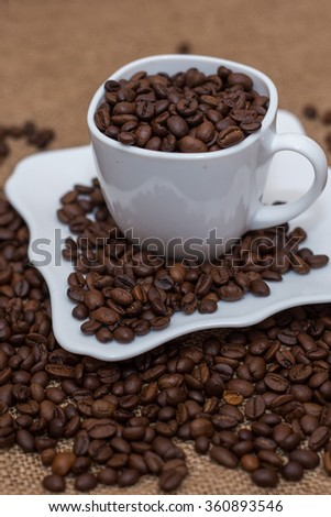 a scattering of coffee beans white cup and saucer on a table brown texture units large lot of grain