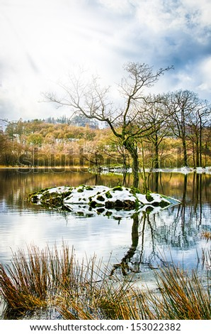 A scene from the English lake district in winter with a tree on an island and winter sun rays - stock photo