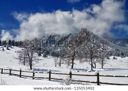 A scenic landscape view of the Boulder Colorado Flatirons with trees and a rustic fence after a nice 13 inch dusting of snow with low hanging clouds. - stock photo