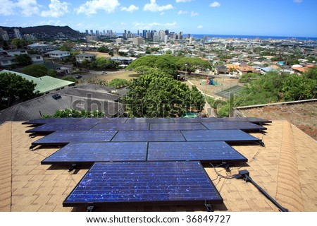 a scenic view of downtown Honolulu, Hawaii, with solar photovoltaic system mounted on a house. - stock photo