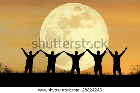 A scenic view of people raising their hands with the full moon in the background - stock photo
