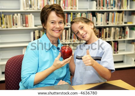 A school boy giving an apple to his teacher and a thumbs-up sign to the camera. - stock photo