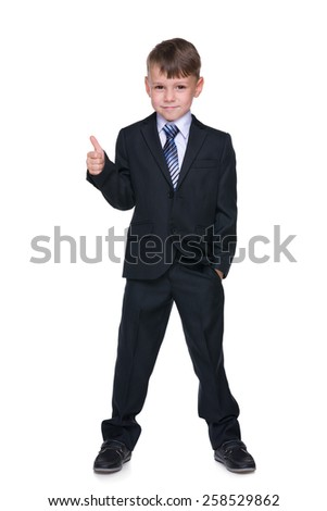 A school boy holds his thumb up on the white background - stock photo