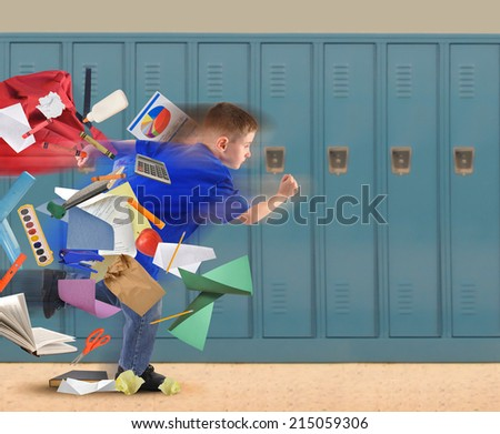 A school boy is running late with school supplies falling out of his book bag in a hallway with lockers in the background for an education or academic concept.  - stock photo