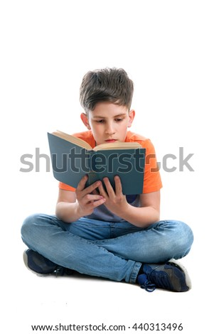 A school-boy is sitting on the floor and reading a book  - stock photo