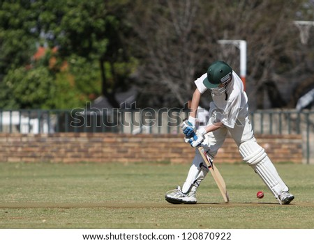 A school boy tries to block a cricket ball and prevent it from hitting his wickets. He is defensive mode but misses. - stock photo