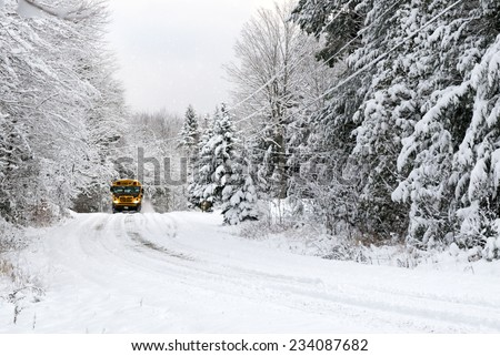 A school bus drives down a snow covered rural country road lined with snow covered trees after a snow storm during the winter season.  - stock photo