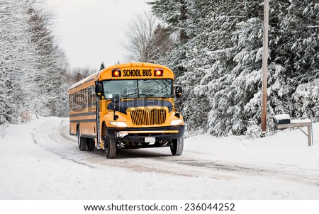 A school bus drives down a snow covered rural country road lined with snow covered trees after a snow storm during the winter season.  Series 3 of 3  - stock photo