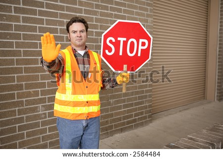 A school crossing guard holding a stop sign.  Room for text. - stock photo