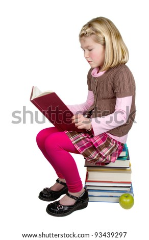 A school girl reading a book sitting on a stack of books, isolated on a white background