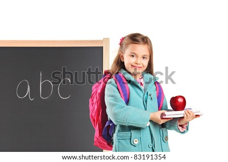 A school girl with backpack holding notebooks and an apple isolated on white background