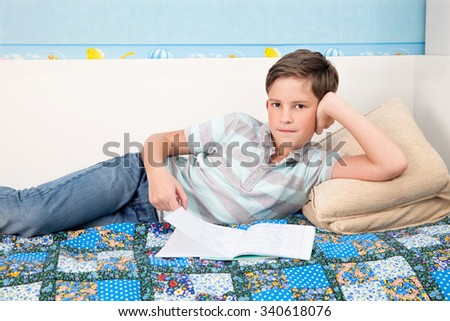 A schoolboy with the notebook lying on the sofa and prepares for the lesson - stock photo