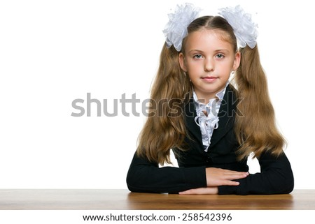 A schoolgirl sits at the school desk against the white background - stock photo