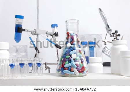 A science beaker full of different colored and shaped pills sits in a lab with other science equipment.